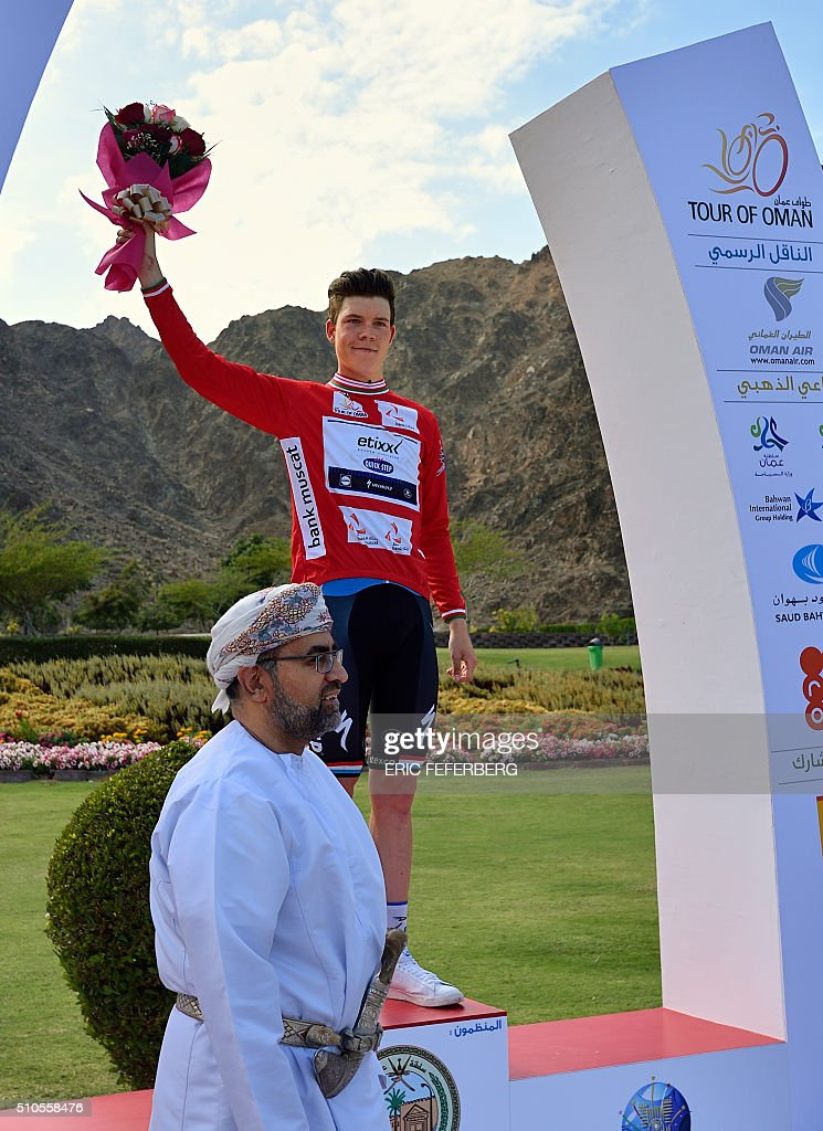 Luxembourg's champion Bob Jungels of Etixx-Quick Step team celebrates with the red jersey during the victory ceremony after he won the first stage of the 7th cycling Tour of Oman between Oman Exhibition Center and al-Bustan on February 16, 2016. / AFP / ERIC