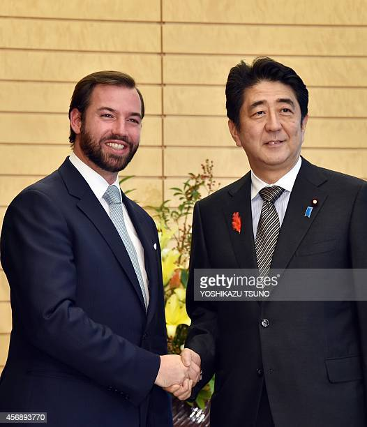 Luxembourg's Crown Prince Guillaume shakes hands with Japanese Prime Minister Shinzo Abe prior to their talks at Abe's office in Tokyo on October 9...