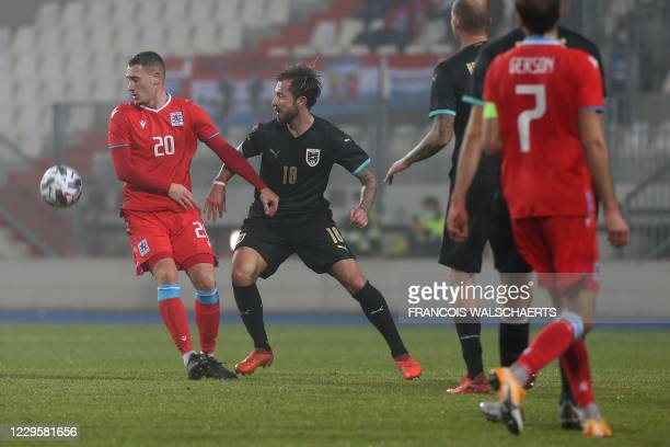 Luxembourg's forward Edvin Muratovic is challenged by Austria's midfielder Louis Schaub during the friendly football match between Luxembourg and...