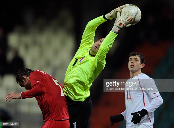 Luxembourg's goalkeeper Jonathan Joubert stops the ball beside Luxembourg's Tom Schnell and Switzerland's forward Admir Mehmedi during the friendly...