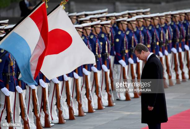 Luxembourg's Grand Duke Henri bows to national flags while reviewing a honor guard during his welcoming ceremony at the Imperial Palace in Tokyo on...