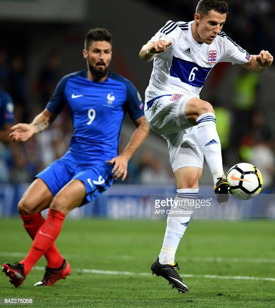 Luxembourg's midfielder Chris Philipps controls the ball ahead of France's forward Olivier Giroud during the FIFA World Cup 2018 qualifying football...