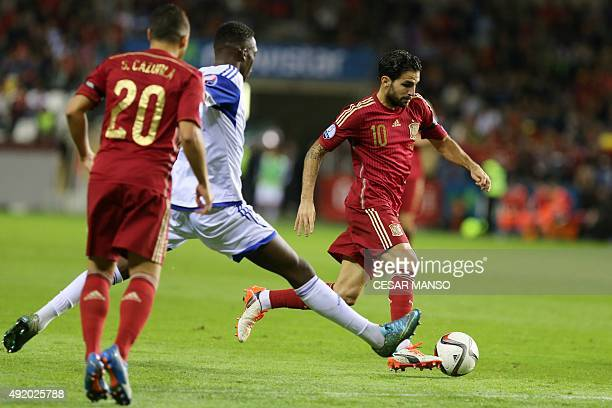 Luxembourg's midfielder Mathias Janisch vies with Spain's midfielder Cesc Fabregas during the Euro 2016 qualifying football match Spain vs Luxembourg...
