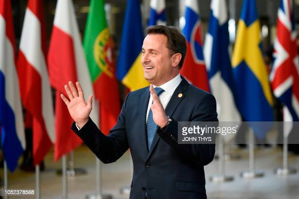 Luxembourg's Prime Minister Xavier Bettel reacts as journalists shout upon his arrival at the European Council in Brussels on October 17 2018 British...