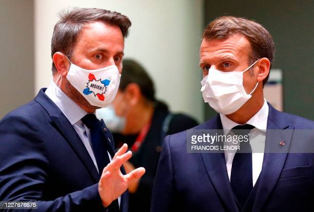 Luxembourg's Prime Minister Xavier Bettel speaks with France's President Emmanuel Macron during an EU summit at the European Council building in...