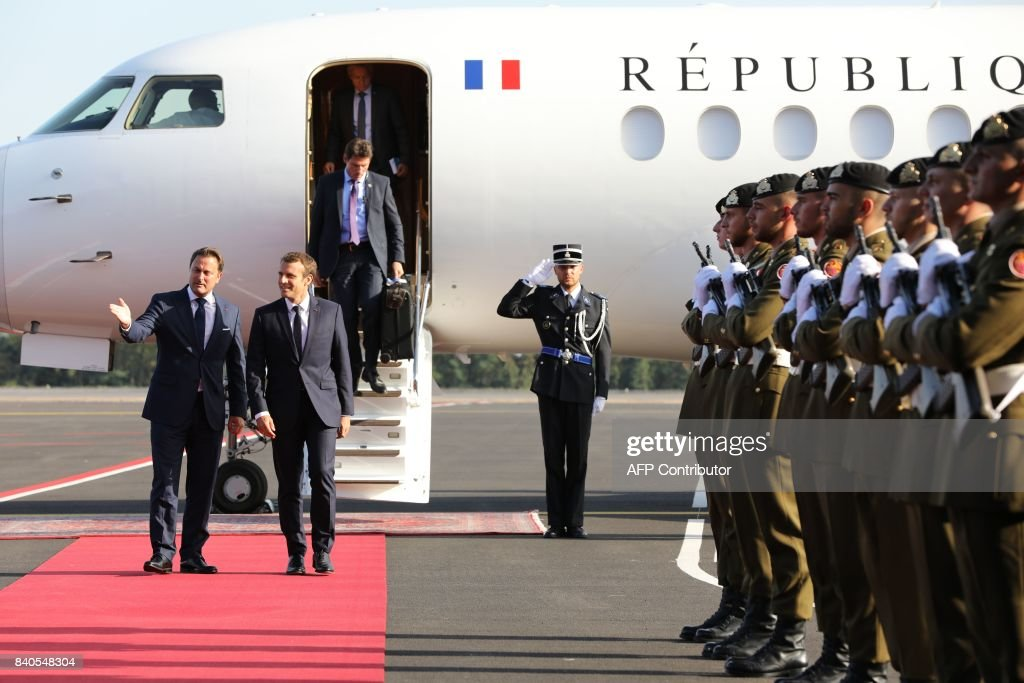 Luxembourg's Prime Minister Xavier Bettel (L) welcomes French President Emmanuel Macron (R) as he arrives at the airport in Luxembourg on August 29, 2017. /