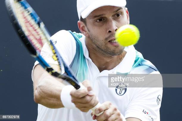 Luxemburg's Gilles Muller returns the ball to Croatia's Ivo Karlovic during the 'sHertogenbosch ATP tennis tournament final match in 'sHertogenbosch...