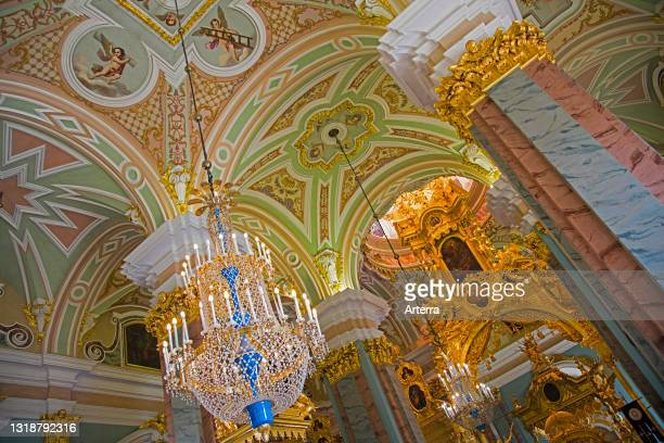 Luxurious crystal chandeliers and vaults with ceiling paintings portraying angels inside the Peter and Paul Cathedral in Saint Petersburg, Russia.