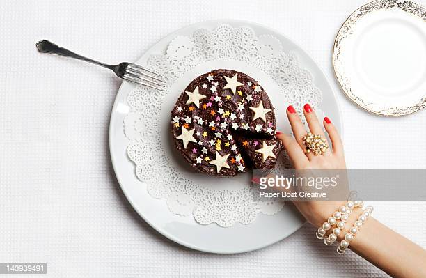 Luxurious hand picking out one slice of cake