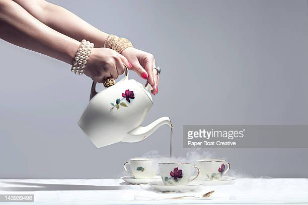 luxurious hand pouring very hot tea