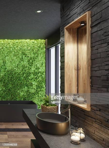 salle de bains moderne luxueuse de spa de maison avec des tuiles noires mates et mur vert de plante de mousse - massage room photos et images de collection