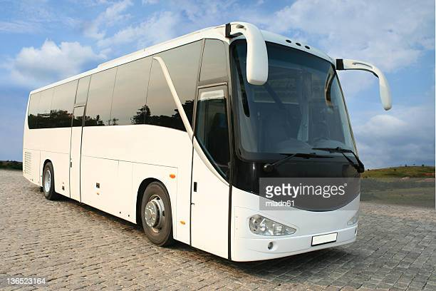 a luxurious white coach with tinted windows - coach bus stock photos and pictures