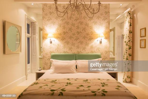 Luxury bedroom with illuminated sconces