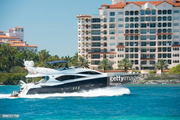 luxury boat drives by fisher island in miami beach florida - fisher island stock pictures, royalty-free photos & images