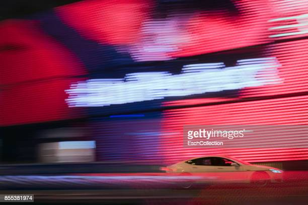 Luxury car passing enormous LED screen in Hong Kong