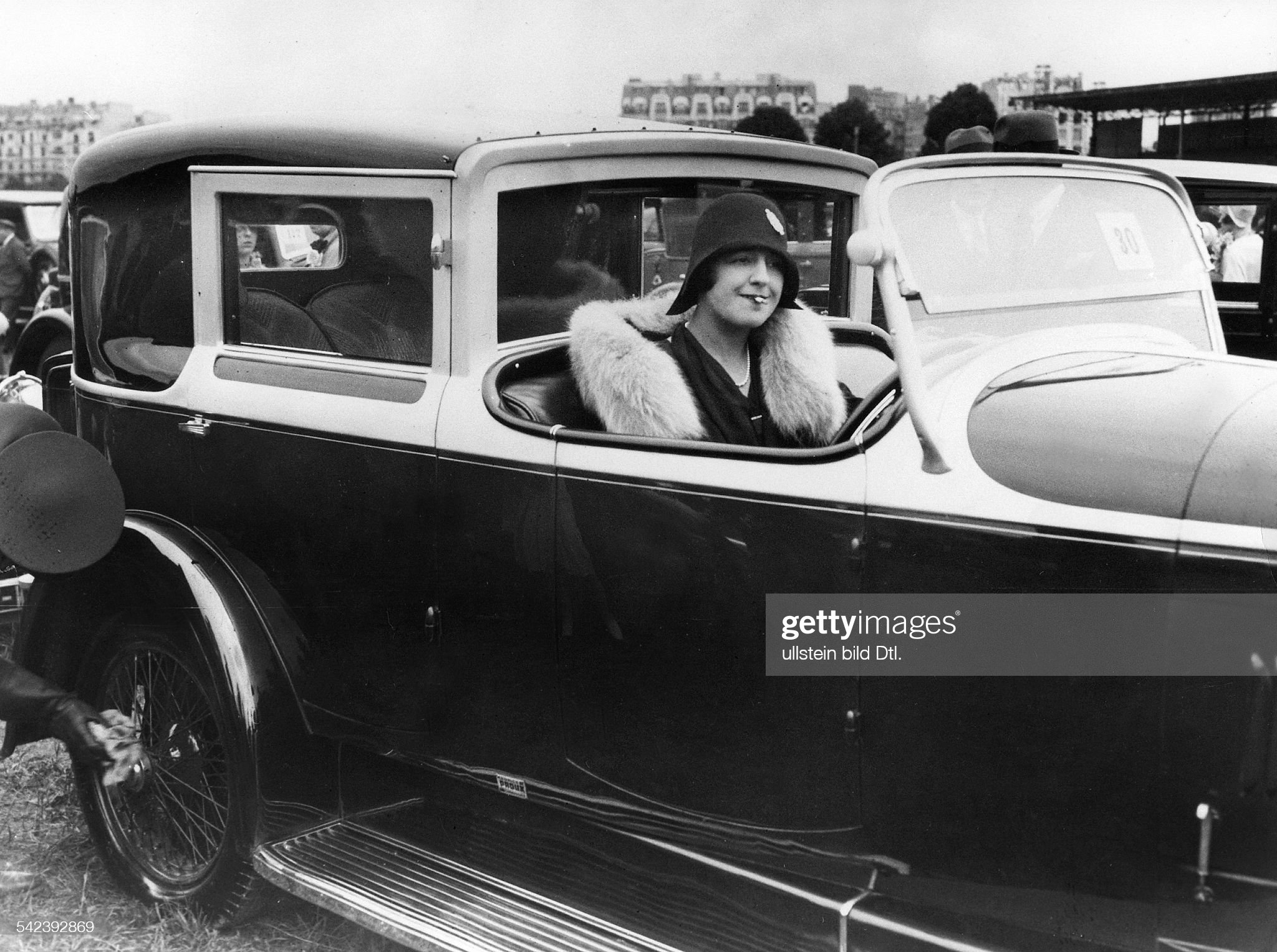 Luxury cars Mrs Mello Rahna behind the wheel of her Bugatti, while the driver polishes the spoke wheels - 1930 - Vintage property of ullstein bild : News Photo