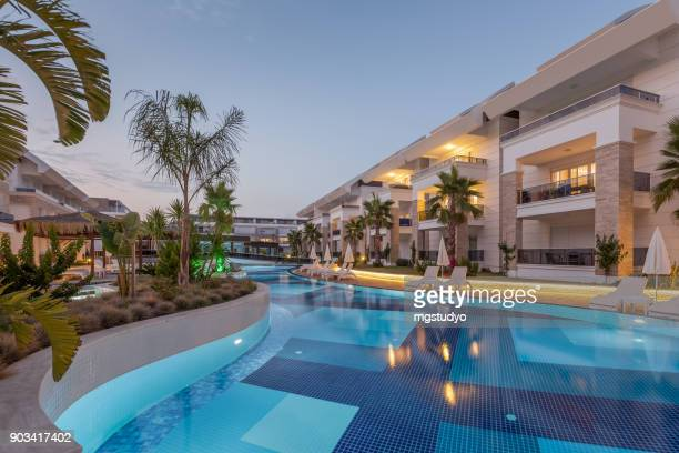 luxury construction hotel with swimming pool at sunset - piscina foto e immagini stock