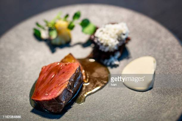 luxury fine dining, grilled sliced steak with pepper sauce on stone plate - ソース ストックフォトと画像