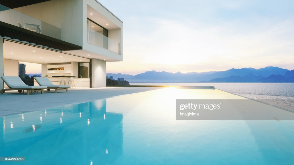 Luxury Holiday Villa With Infinity Pool At Sunset Stock Photo