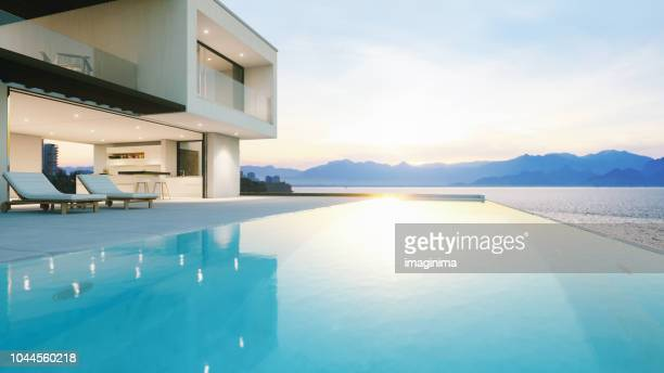 luxury holiday villa with infinity pool at sunset - moderno foto e immagini stock