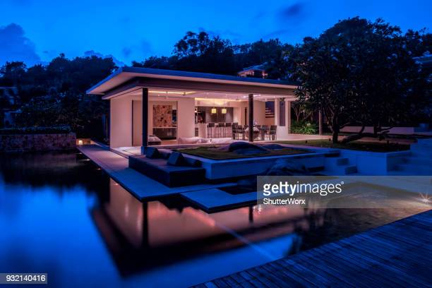 luxury home island villa at twilight with trees and reflections in water - d'atmosfera foto e immagini stock