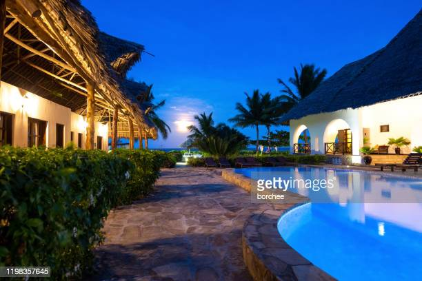 luxury hotel with swimming pool at night - butlins stock pictures, royalty-free photos & images