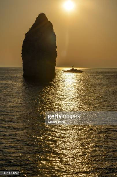 LIPARI SICILY MESSINA ITALY A luxury motor boat is moored by a 'faraglioni' or stack rock formation off the coast of Lipari Italy at sunset