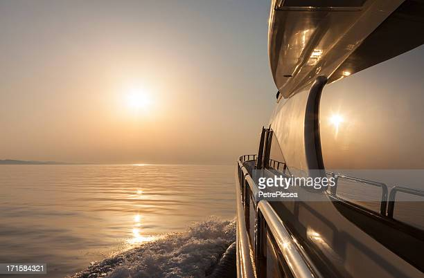 Luxury motor yacht sailing at sunset