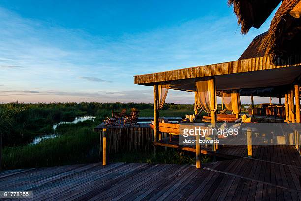 A luxury safari camp overlooking a wetland at dawn.