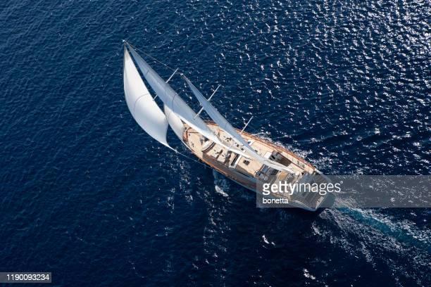 luxury sailboat sailing in the open blue sea - barca a vela foto e immagini stock