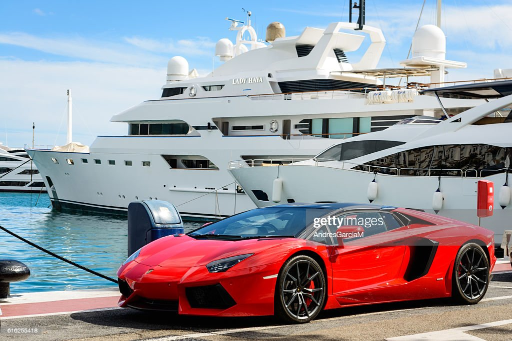 Luxury sports car and yachts at Puerto Banus in Marbella : Foto de stock
