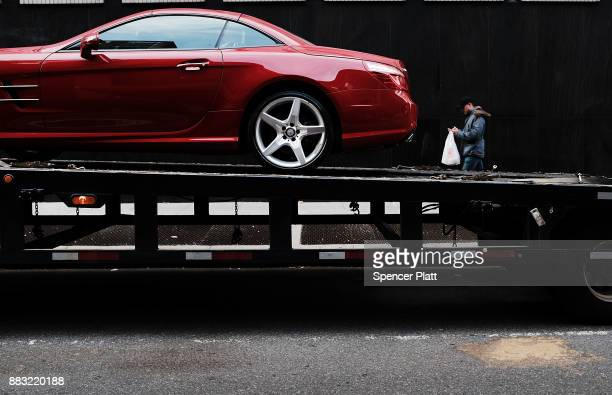 A luxury sports car sits on a truck along a Manhattan street on November 30 2017 in New York City Republicans are coming closer to getting the votes...