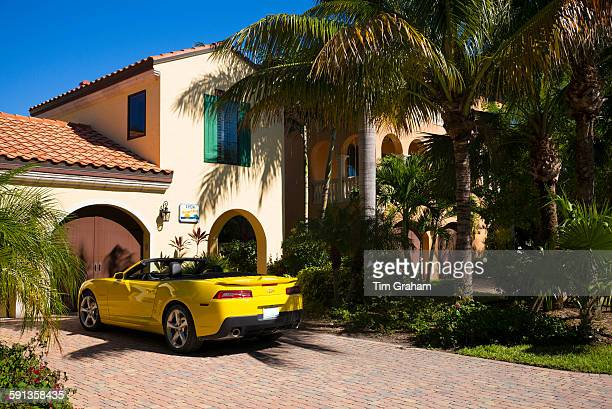 Luxury stylish winter home and yellow drop head convertible Chevrolet Camaro R5 sports car Captiva Island Florida USA