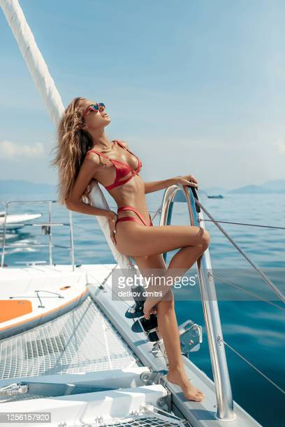 luxury vacation: beautiful blonde woman in open water sea on yacht wearing sexy red bikini and red sunglasses. summer time. holidays in a tropical islands - seductive women stock pictures, royalty-free photos & images