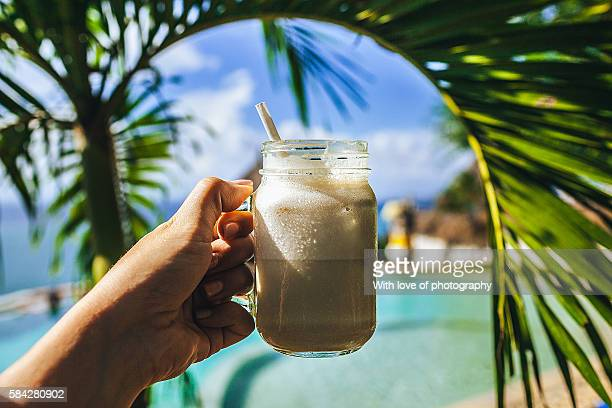 Luxury vacations in paradise, hand holding chocolate milkshake in a glass with tube and a palm leaf on tropic island