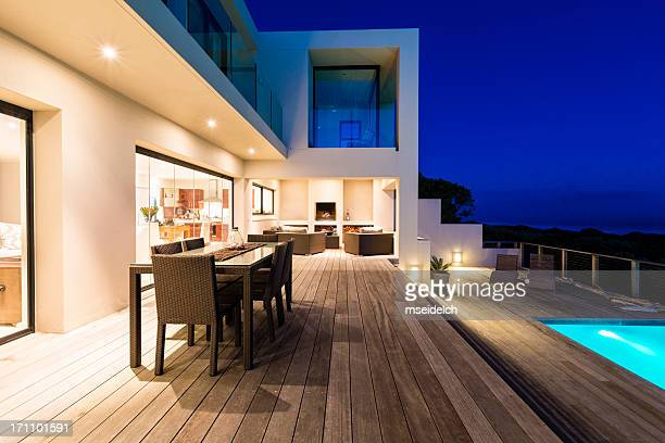 luxury villa pool deck at dusk - illuminate stock photos and pictures