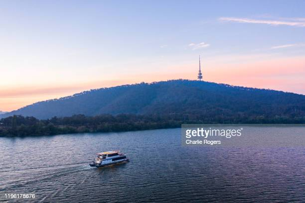 luxury yacht at lake burley griffin and telstra tower at sunset - canberra photos et images de collection
