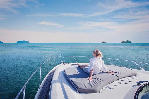 luxury yacht travel, woman enjoying cruise onboard 1057327834