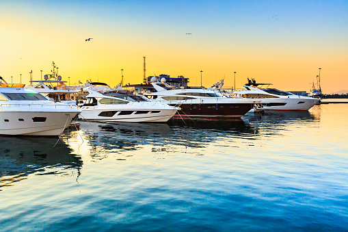 Luxury yachts docked in sea port at sunset. 947836028