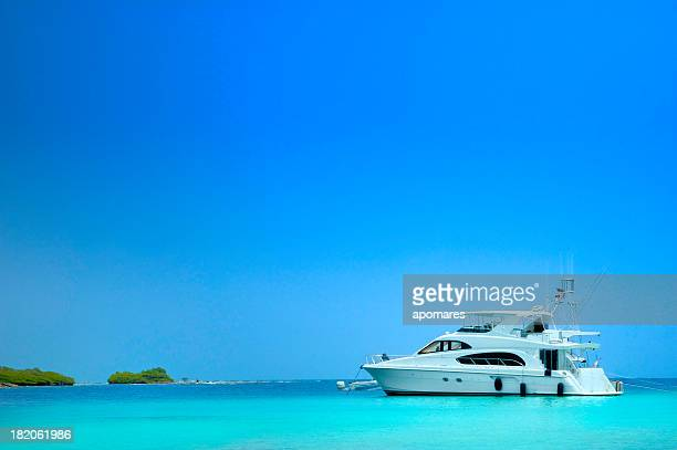 luxury yachts sailing in a tropical exotic island beach - luxury yacht stock pictures, royalty-free photos & images