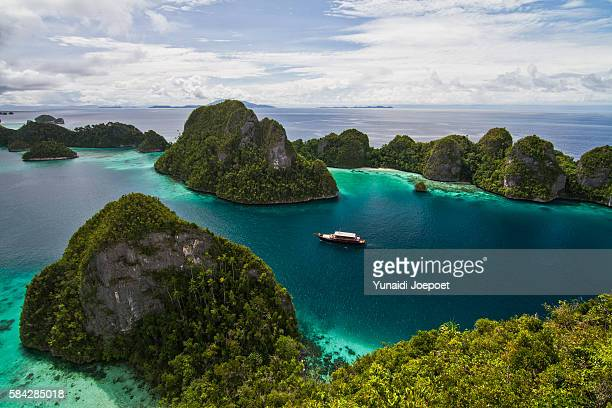 luxury yatch sailing in beautiful island, raja ampat, indonesia - raja ampat islands stock photos and pictures