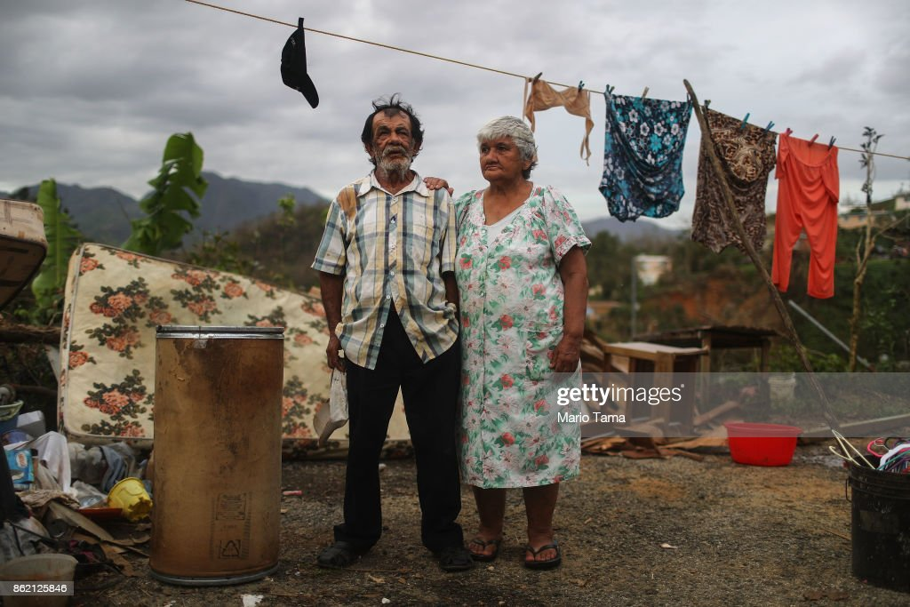 Luz Sota Rivera (R) and Francisco Nazario Aviles pose outside their damaged home, with debris removed from their home uncollected in the driveway, three weeks after Hurricane Maria hit the island, on October 12, 2017 in Jayuya, Puerto Rico. The area is without running water or grid power as a nightly curfew remains in effect. Only 17 percent of Puerto Rico's grid electricity has been restored. Puerto Rico experienced widespread damage including most of the electrical, gas and water grid as well as agriculture after Hurricane Maria, a category 4 hurricane, swept through.