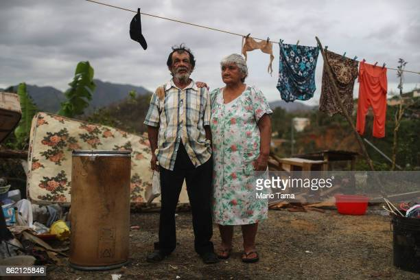 Luz Sota Rivera and Francisco Nazario Aviles pose outside their damaged home, with debris removed from their home uncollected in the driveway, three...