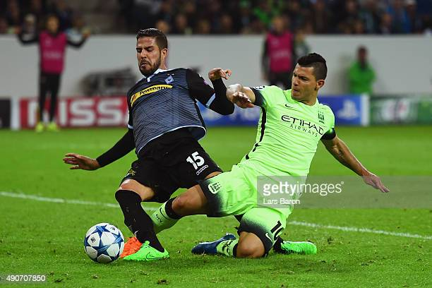 Álvaro Domínguez of Borussia Monchengladbach is tackled by Sergio Aguero of Manchester City during the UEFA Champions League Group D match between...