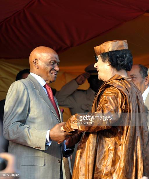 Lybian head of state Mouammar Kadhafi speaks with Senegal's President Abdoulaye Wade during the World Festival of Black Arts and Culture in Dakar on...
