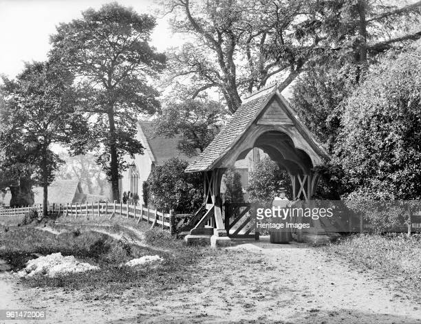Lychgate, St Mary's Church, Aldworth, Berkshire, 1895. Looking towards the church which is visible through the trees with a woman passing through the...