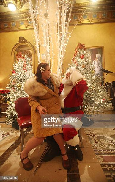 Lycia Ferguson clowns around with Santa Claus in the lobby of the Roosevelt Hotel decorated with Christmas lights December 1, 2009 in New Orleans,...