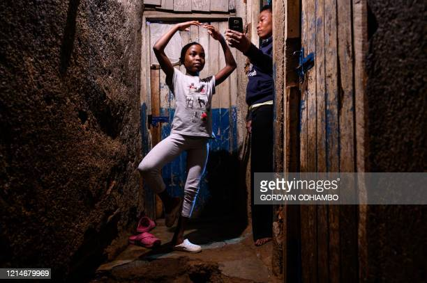 Lydia Akoth a member of Project Elimu practises dancing after moving from her living room to a corridor for a steady floor during a distant ballet...