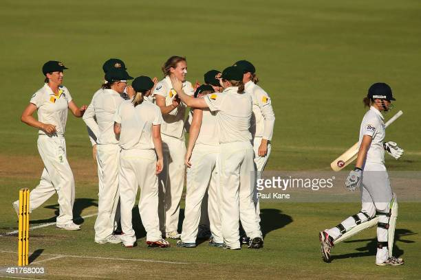 Lydia Greenway of England walks back to the rooms while Ellyse Perry of Australia celebrates her wicket with team mates during day two of the Women's...