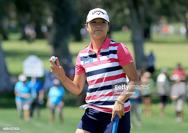 Lydia Ko of New Zealand acknowledges the crowd on the green at the par 5 9th hole after holing out a par putt to end her round of 1 under par 71 to...